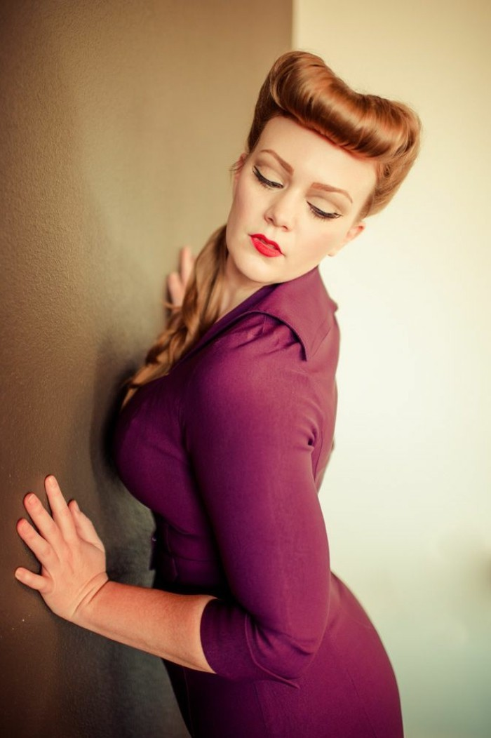 vintage hairstyles, woman with copper ginger hair, ponytail and curled bangs, wearing a purple-maroon dress, leaning on wall with closed eyes