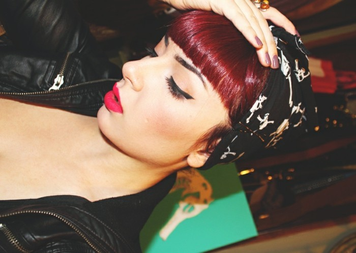 bettie bangs, sideways photo of woman with burgundy hair and bangs, black eyeliner and dark hot pink lipstick, wearing black leather jacket and black bandanna with white skull pattern