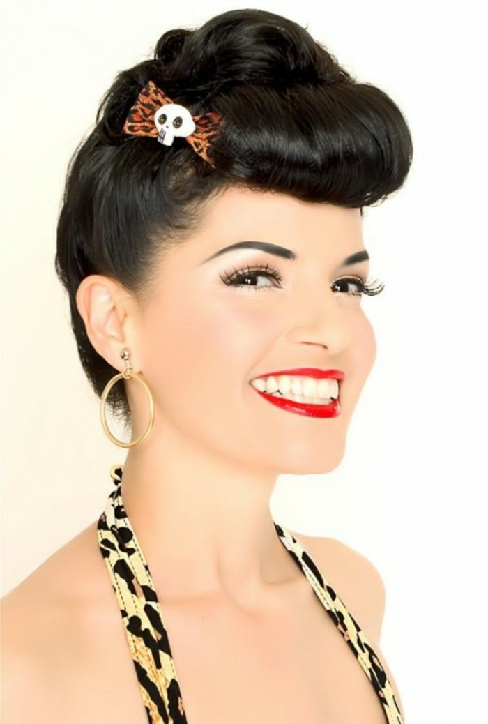 betty bangs, woman with short black hair styled in an updo, animal print bow with skull detail, red lipstick fake lashes big white teeth