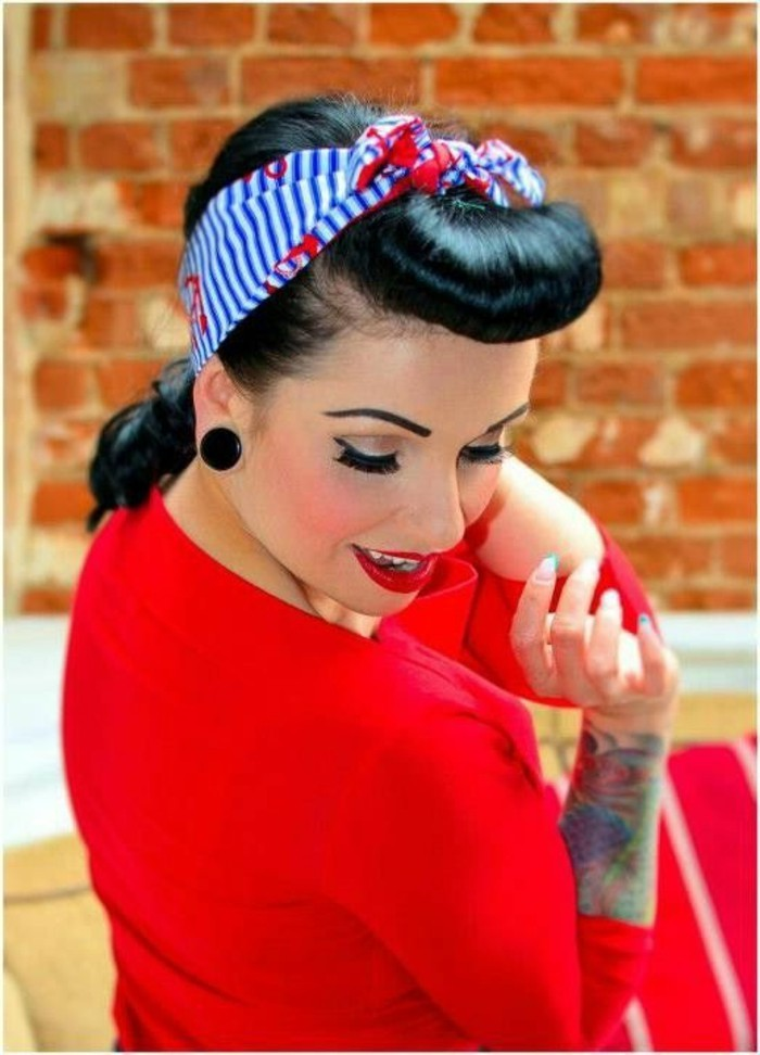 betty bangs, smiling black-haired woman seen from above, blue and white striped bandanna with red flowers, curled bangs, wearing red top and lipstick, fake eyelashes and mascara, big black earrings and tattoos on arm