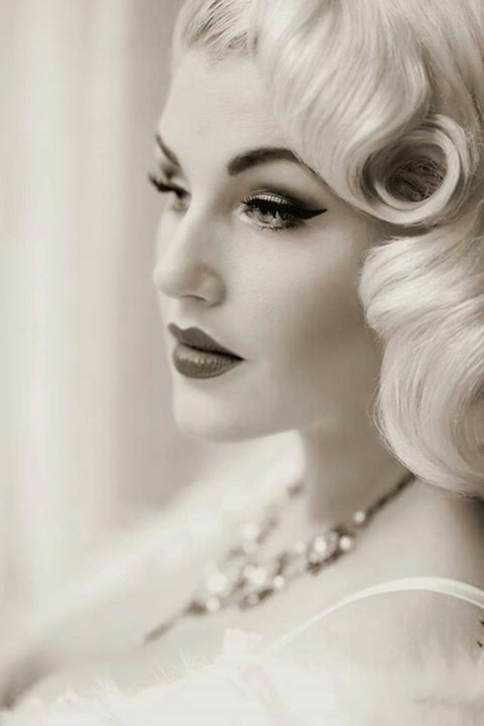 black and white image of a blonde woman, retro curls and heavy make up, eyeliner and lipstick, mascara and fake eyelashes