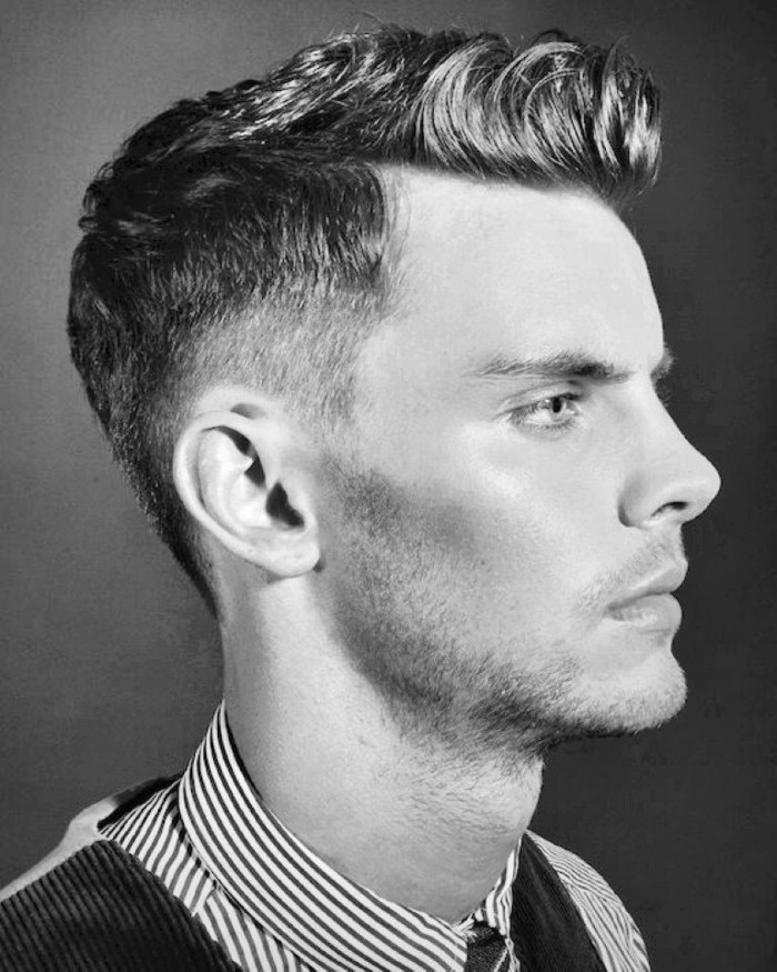 serious-looking young man with short hair and gelled up bangs, in profile with stubbly chin, pinstriped shirt and formal vest, black and white photo