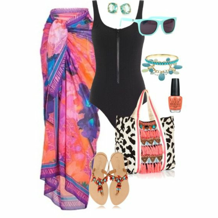 black swimsuit, near large floral sarong in orange pink and blue, sunglasses and earrings, bracelets and nail polish, large beach bag and sandals