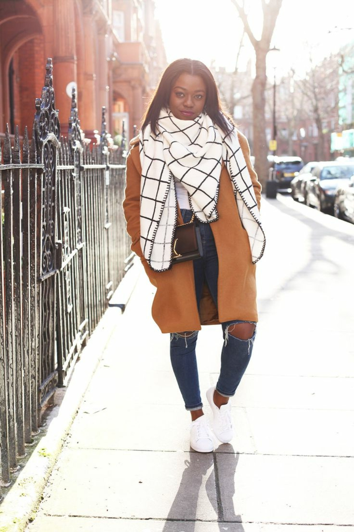 black woman with straight dark brown hair, wearing big white and black chequered scarf, soft orange coat and skinny jeans, with white sneakers and brown shoulder bag