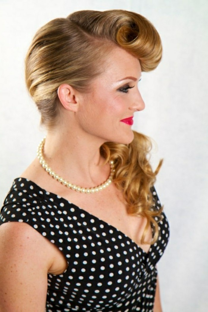 bettie bangs, blonde woman with curled bangs and long hair in ponytail, red lipstick and heavy eye make up, pearl necklace and black top with white polka dots