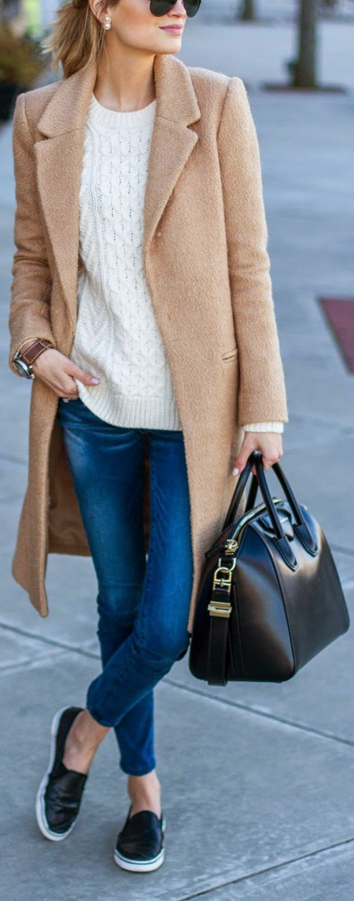 long camel brown coat over white sweater, blue jeans and black leather slip-on shoes, worn by blonde woman with sunglasses, holding black leather bag