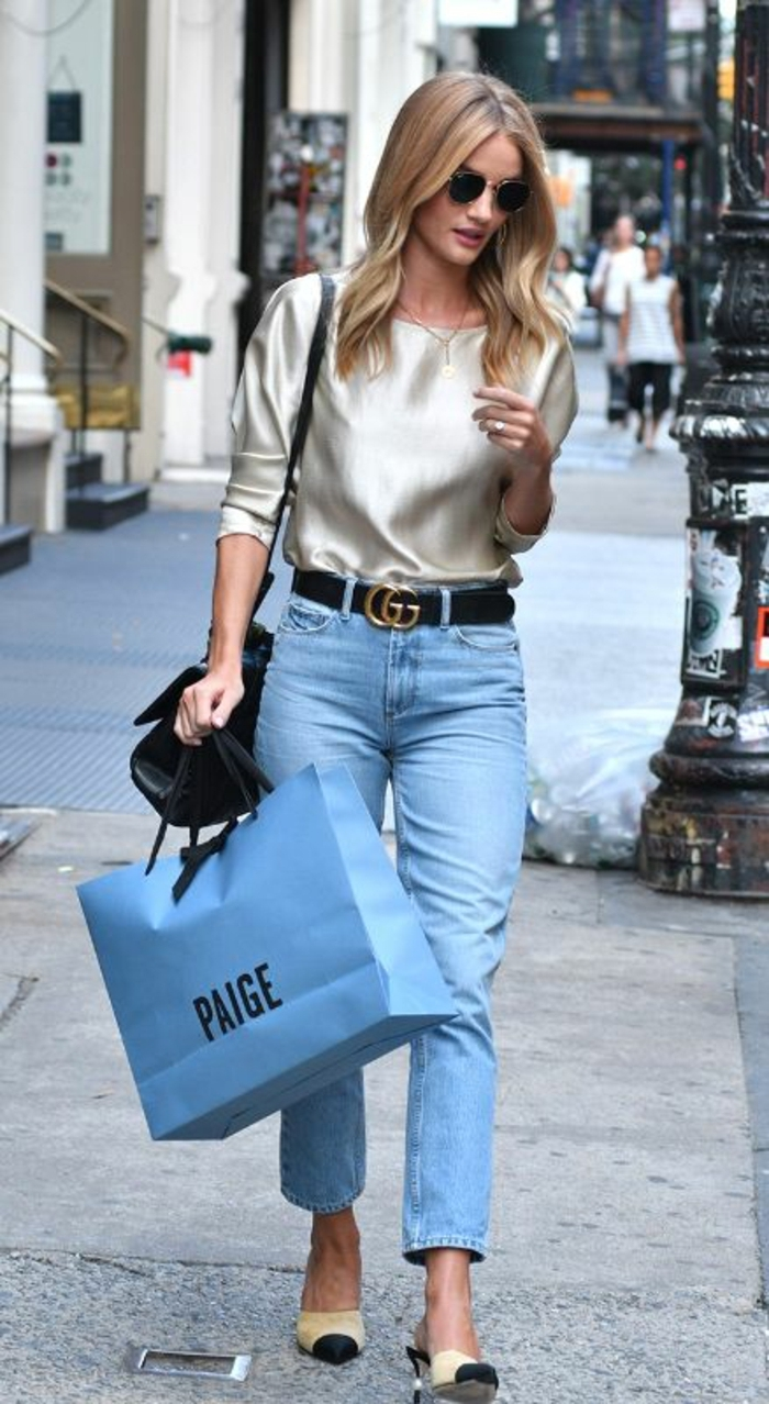 blonde woman with black sunglasses, wearing metallic top and vintage jeans, black belt and cream and black flat shoes, black shoulder bag and blue paper shopping bag