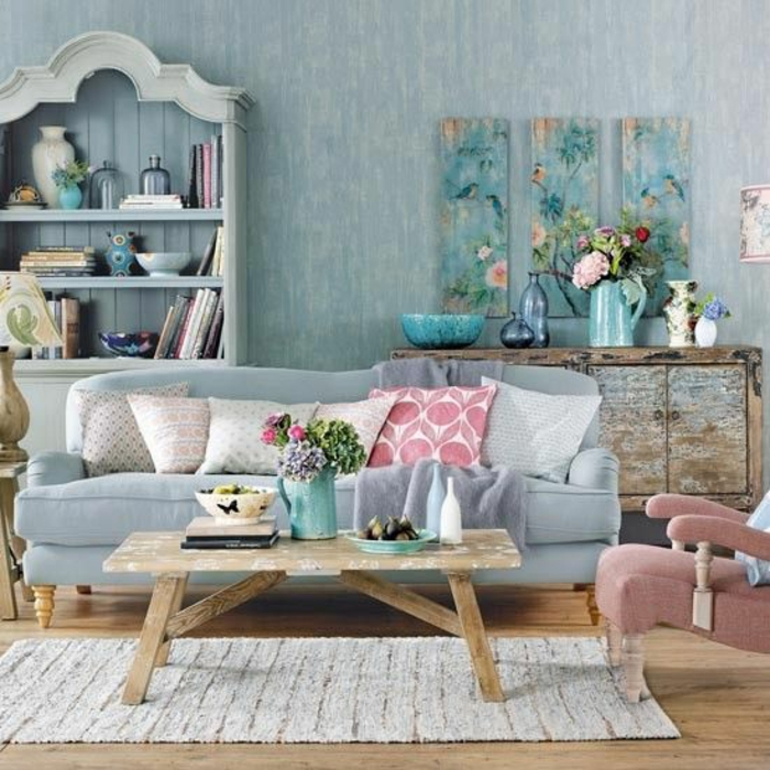 interior painting, pale blue wallpaper, pale blue pastel colored cupboard and sofa, six pastel colored cushions, pastel pink chair, pale wooden table and wooden floor, pale cream rug, artwork decorations and flowers