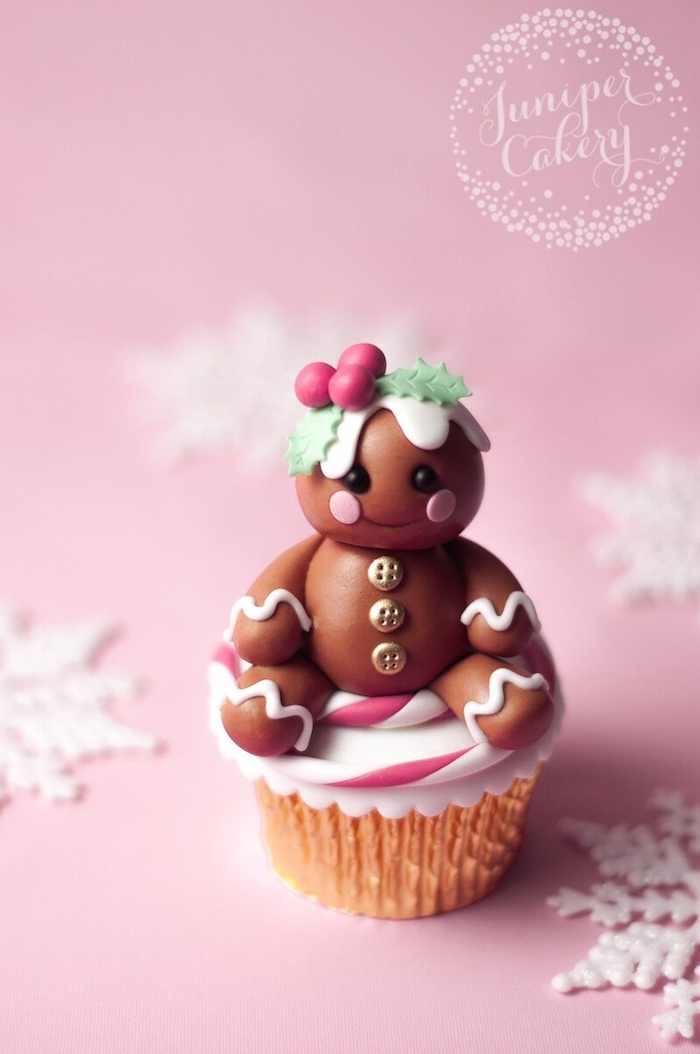 cupcake with golden wrapper, decorated with a little brown fondant doll-like shape, golden buttons and holly in hair