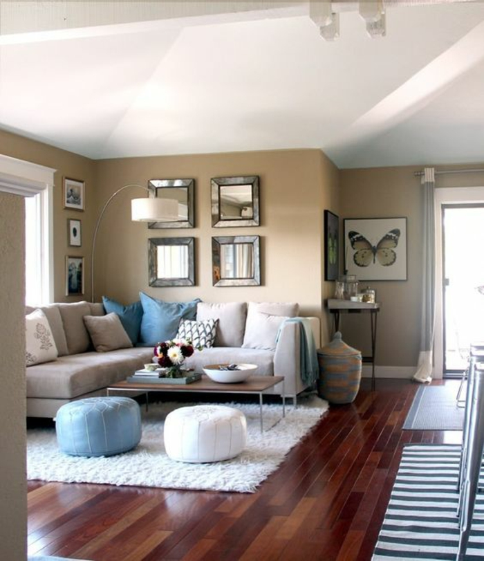 white ceiling and dark wooden floor, pale brown walls,big light grey sofa with blue grey and patterned cushions, white fluffy carpet and two bean floor cushions
