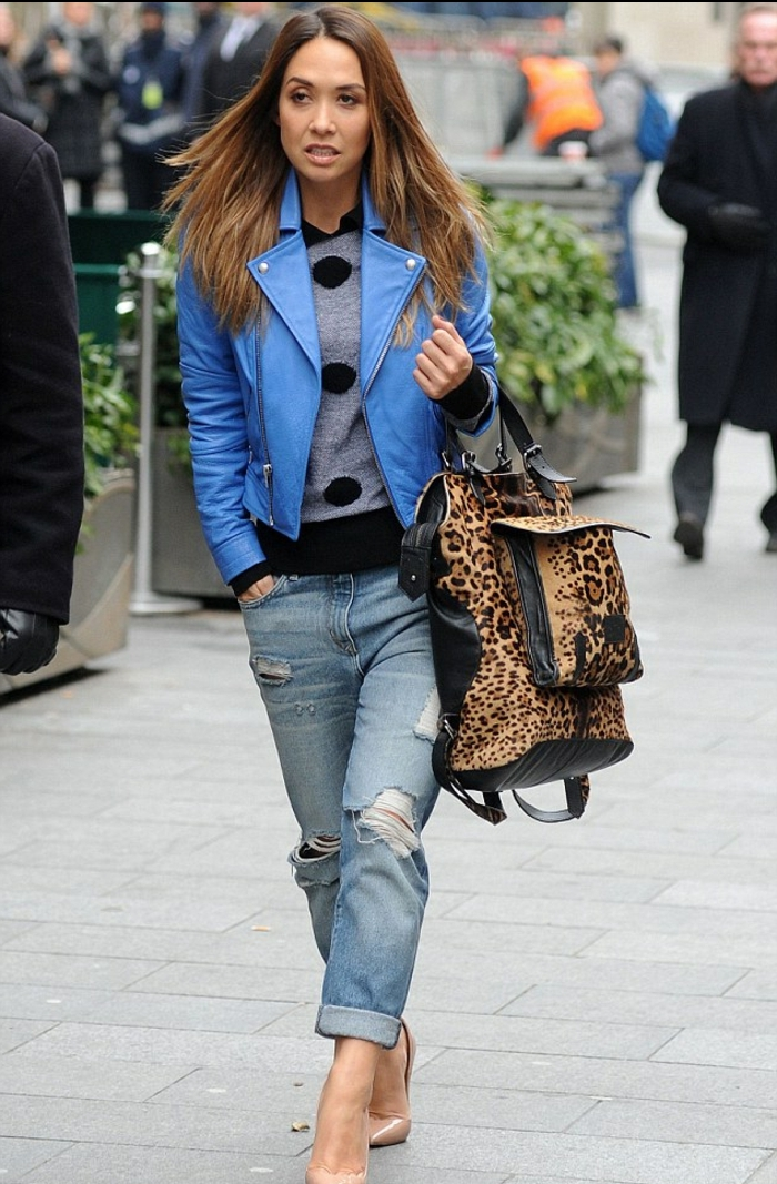 casual business attire, brunette woman with bright blue leather jacket, distressed and torn jeans, black and grey top, nude pink shoes and big animal print bag