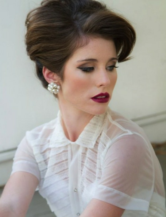 woman with dark red lipstick and heavy eye makeup, fake lashes eyeliner mascara, sheer white top and white cardigan underneath, pearl earrings and brown hair in retro updo