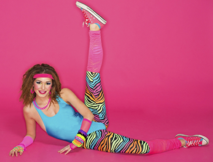 80s clothing, smiling brunette with curly hair, exercising in a neon blue bodysuit with animal print leggings, pink legwarmers mesh arm-warmers and sneakers, neon bangles necklace headband hoop earrings