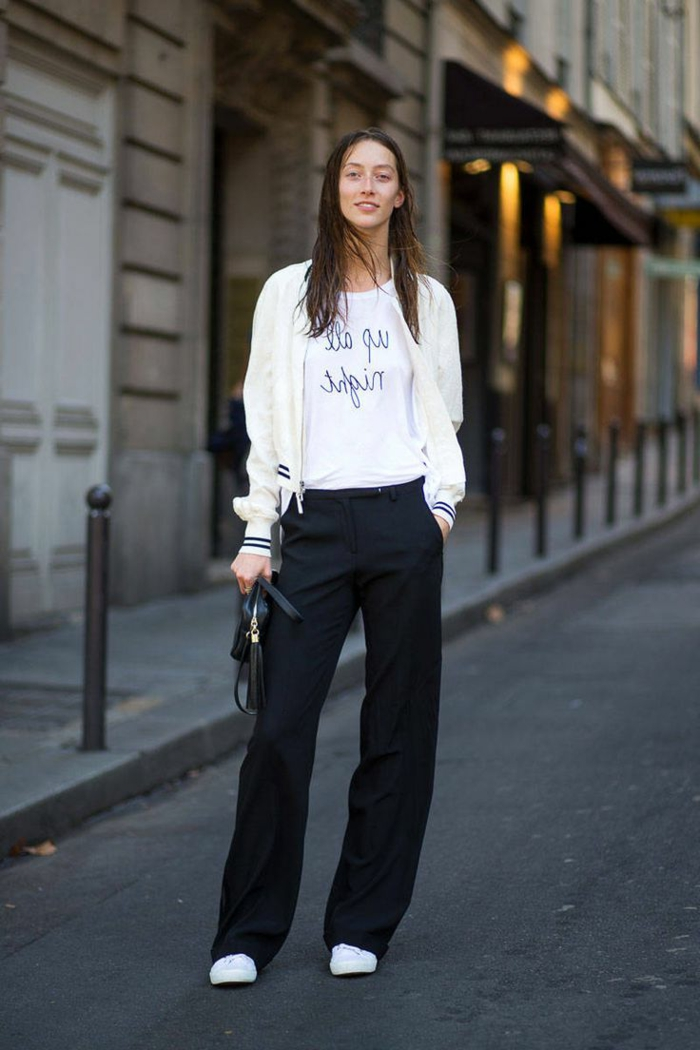 smiling brunette woman, wearing white baseball jacket, over white t-shirt with black print, with long black trousers and white sneakers, holding small black handbag