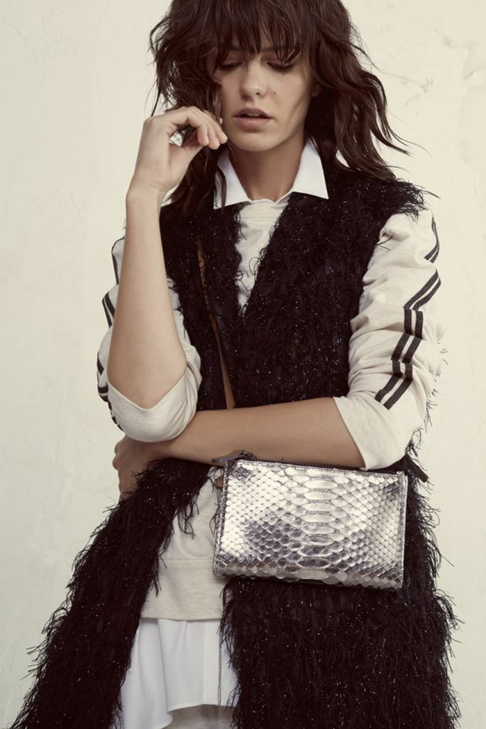 woman with messy brown hair and bangs, wearing long black fluffy fur black gilet, over white shirt with two black stripes on sleeves, small shiny silver snake leather bag