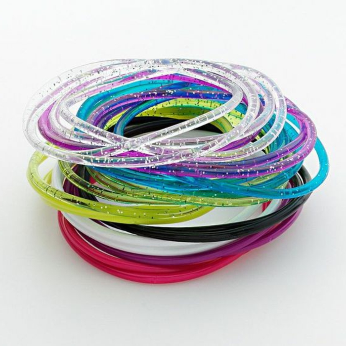 thin plastic sparkling gel bracelets, neon pink blue and green, white black purple and clear, white background
