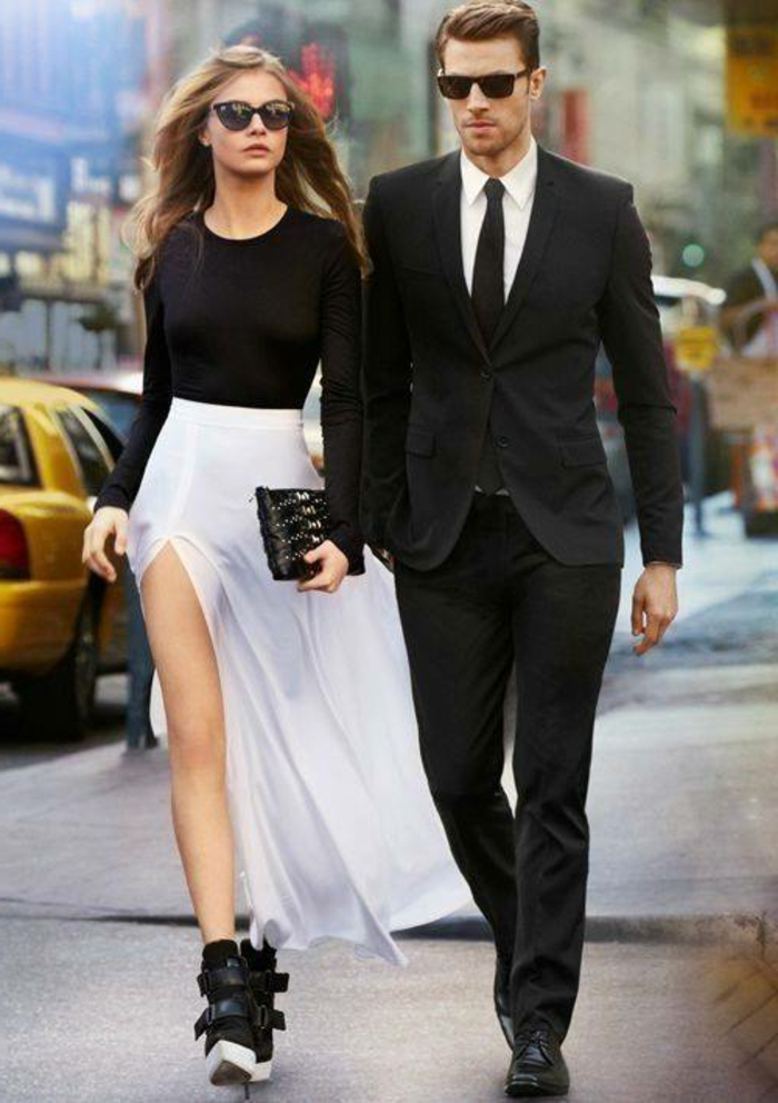 blonde woman with sunglasses, wearing black top and floaty white skirt, with black clutch and ankle boots, next to a man in black formal suit, black tie shoes and sunglasses