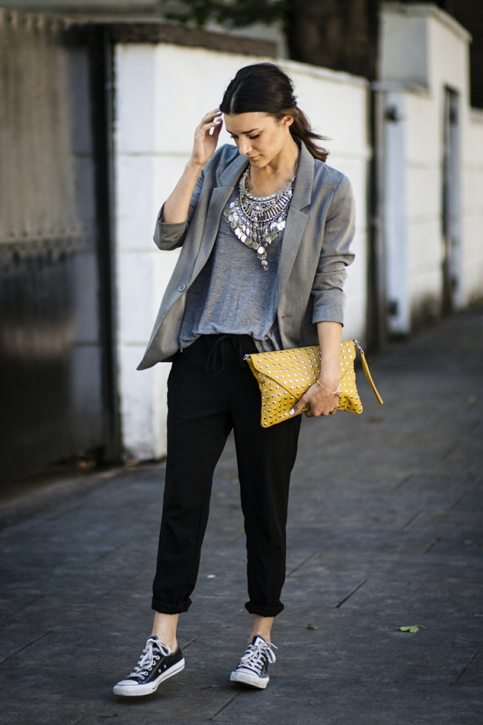 business casual attire for women, black ankle-length sports pants, grey top and grey blazer, plain sneakers and yellow clutch, worn by woman with dark hair and big elaborate silver necklace