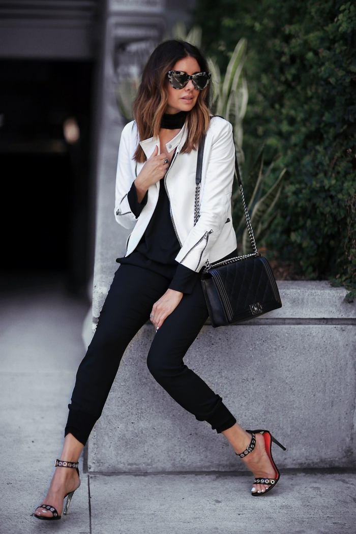 interview outfits for women, skinny calf-length trousers, white leather jacket over black top, black and red strappy sandals with studs, black shoulder bag worn by woman with sunglasses