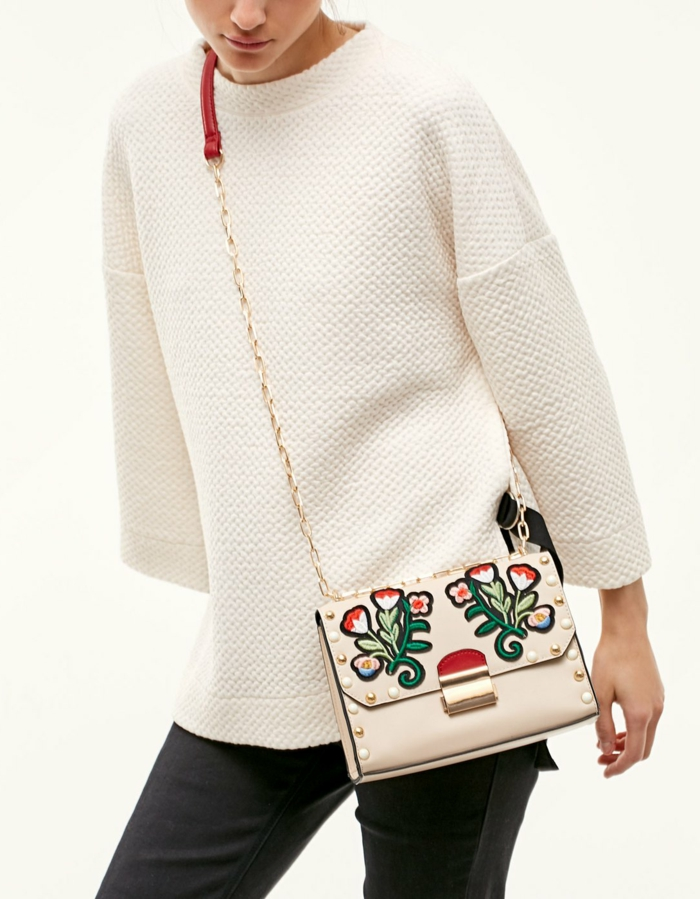 business attire for women, woman with white loose top, black skinny trousers, white embroidered cross-body bag