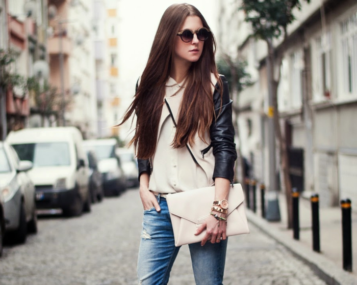 casual business attire, woman with long brown hair, white and black cropped leather jacket, blue distressed jeans and white shirt, white clutch and sunglasses