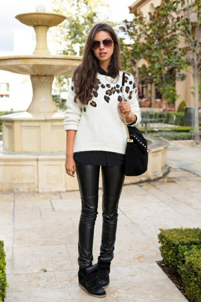 business attire for women, skinny black leather trousers, black shoes and shirt, white sweater with animal print detail, on brunette woman with sunglasses