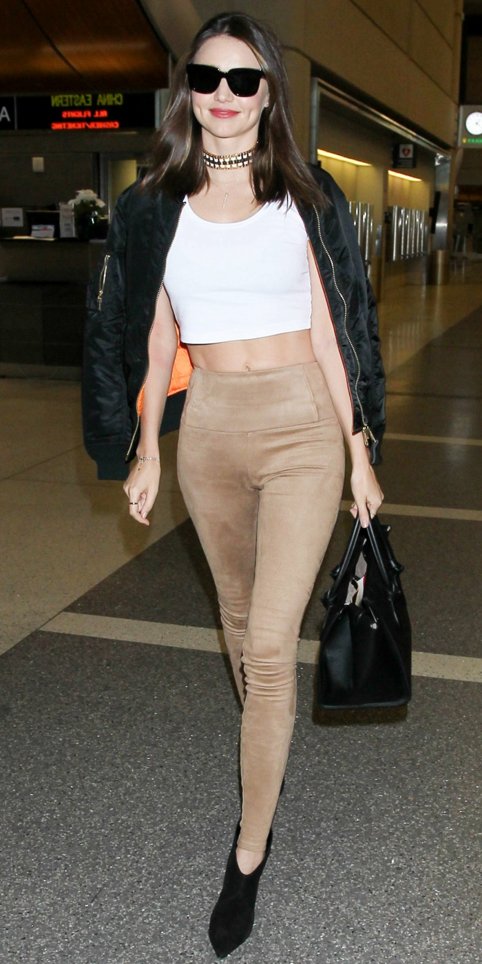 smiling brunette woman with sunglasses, wearing white crop top, skinny camel trousers and black ankle boots, black bomber over shoulders, with chocker necklace and black bag