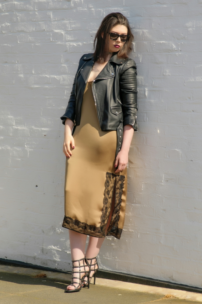 business attire for women, camel-brown satin dress with lace details, black biker leather jacket, sunglasses and high heels on brunette woman