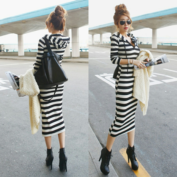 business casual dresses, woman with hair in messy bun, wearing oversized black and white striped sweater dress with hood, holding white cardigan and magazine, black shoes and leather bag, seen from back and front