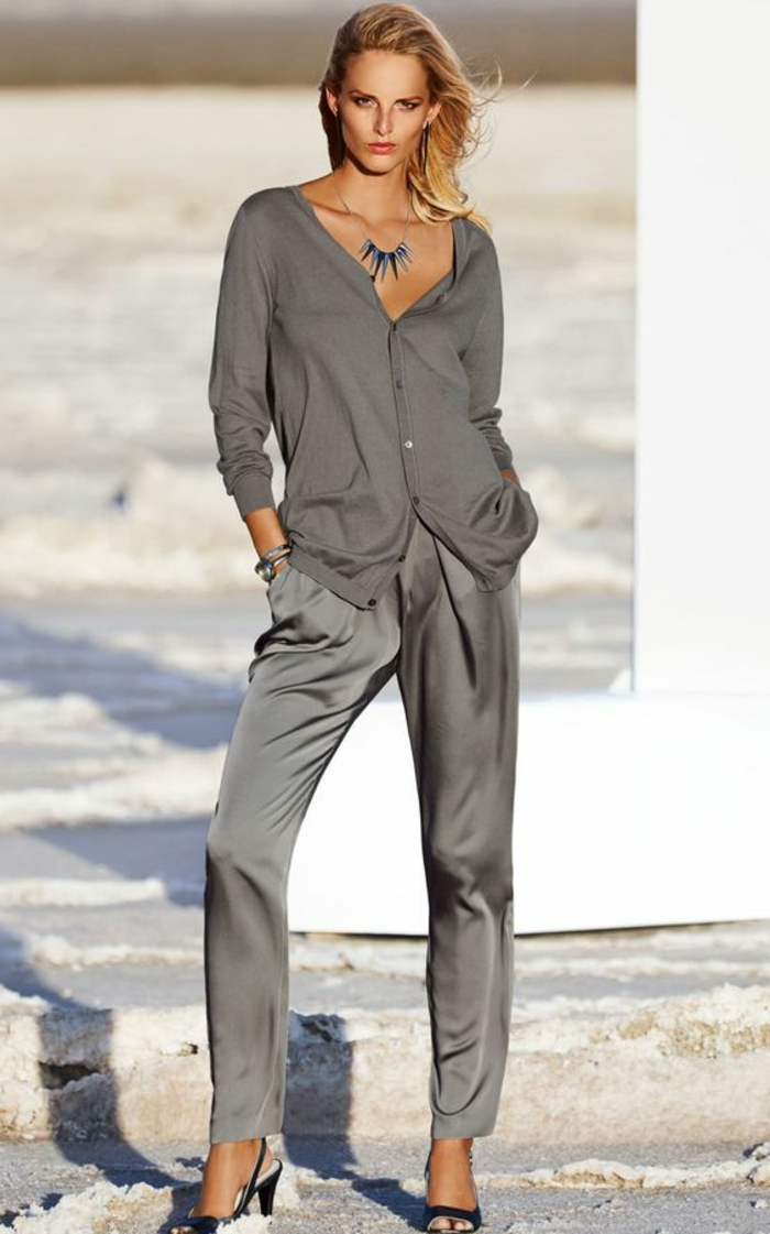 business casual for women, blonde woman wearing grey shiny trousers, grey cardigan and a necklace