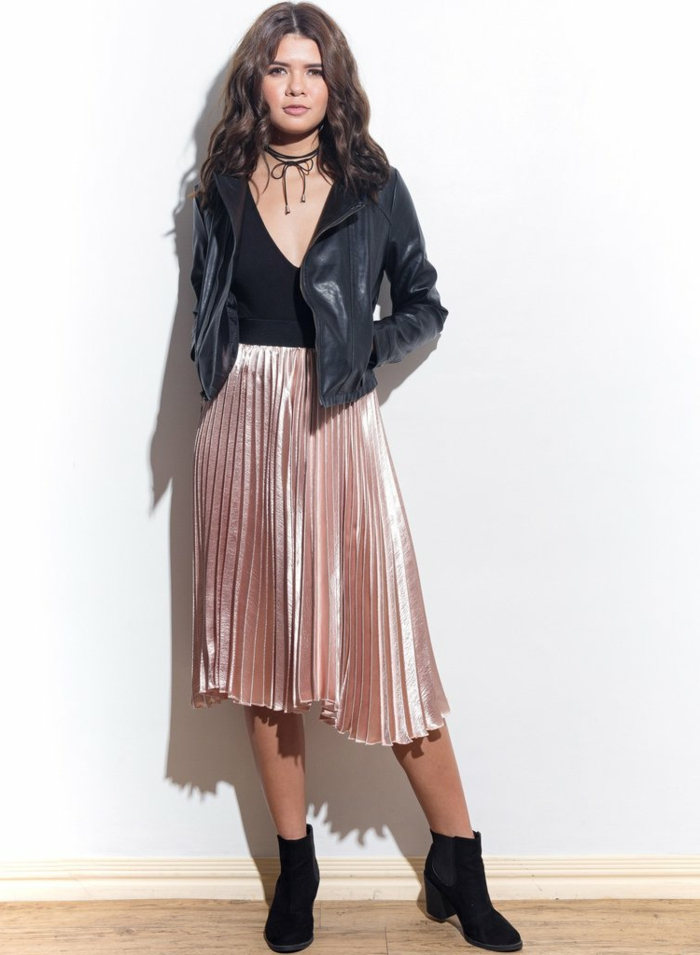 casual business attire, curly-haired brunette with shiny pink pleated ankle-length skirt, black leather biker jacket over black top, chocker and black ankle boots