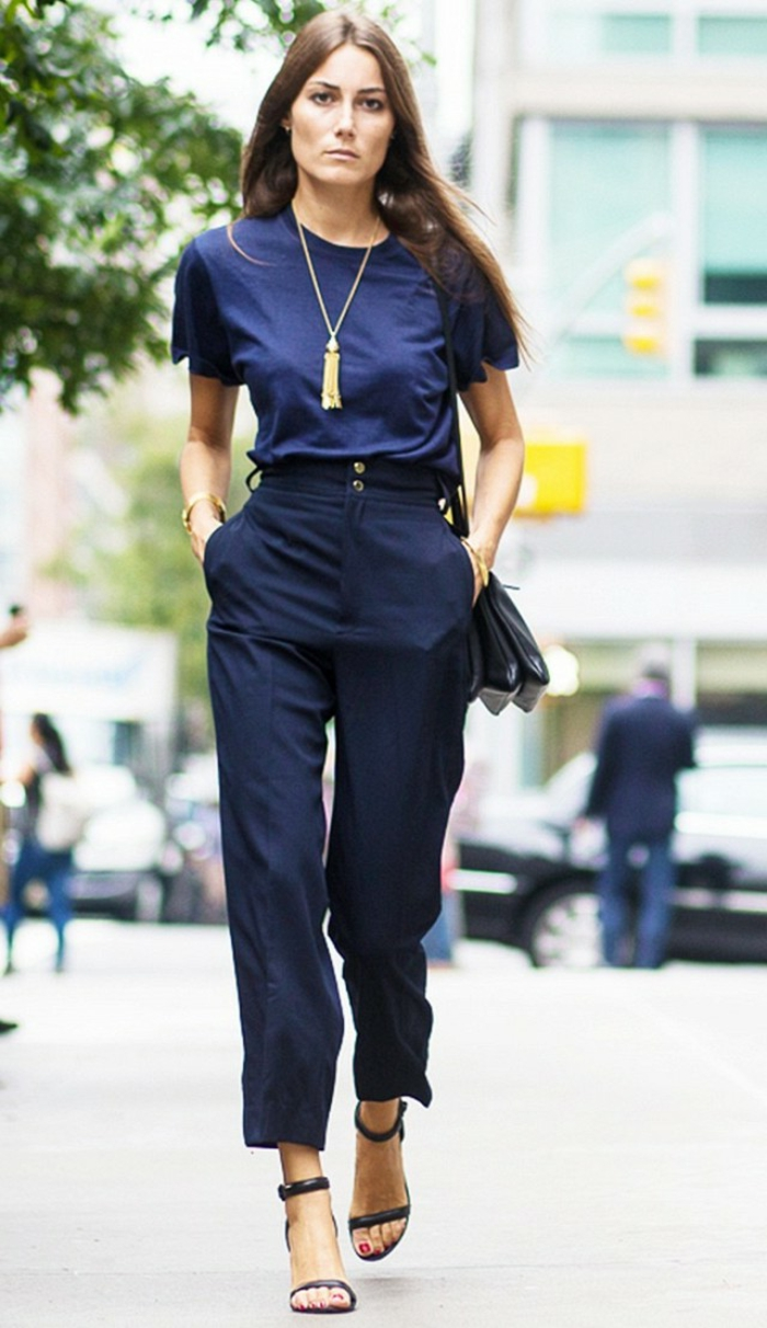 interview outfits for women, serious brunette woman, wearing high-waisted navy trousers, high-heeled sandals and black bag, dark blue t-shirt and golden necklace