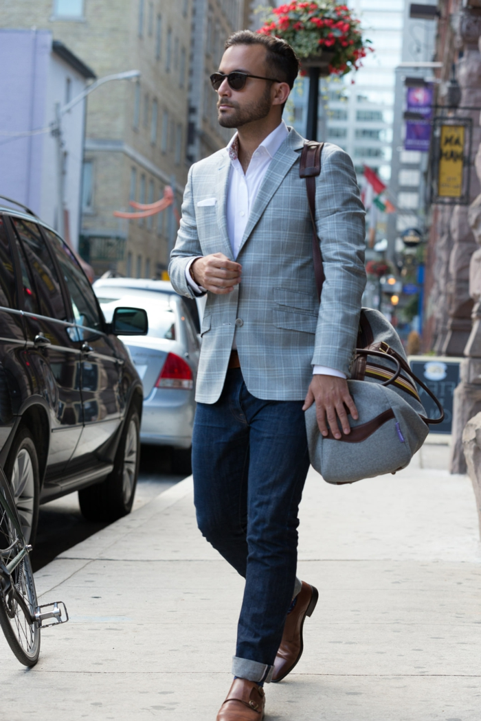 business professional attire, man with jeans and brown leather shoes, wearing light grey chequered blazer over pale pink shirt, with sunglasses and sports bag