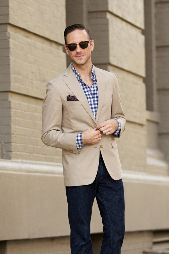 business professional attire, man with gelled back hair, light brown blazer with handkerchief, over white and blue chequered shirt, dark blue jeans and sunglasses
