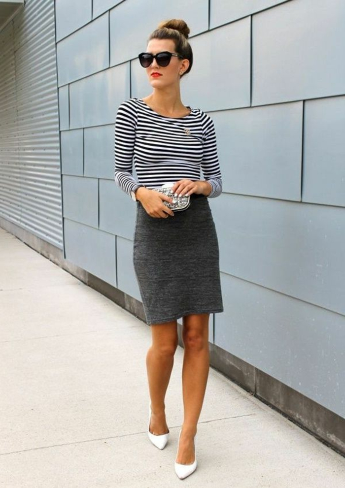 business casual attire for women, dark grey mini skirt, white and black striped top, white high heels and small clutch, worn by woman with sunglasses and hair bun