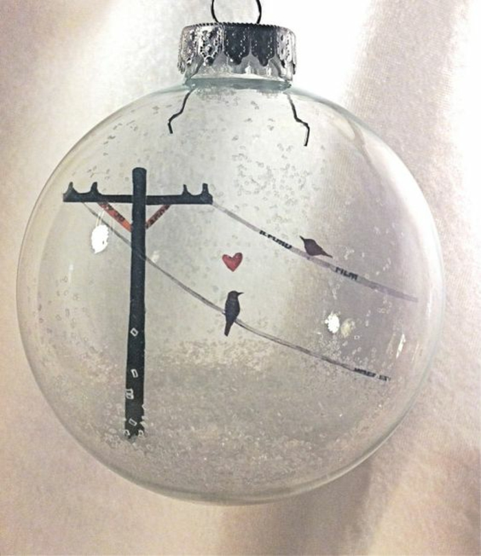cheap christmas gift ideas, one clear glass bauble with silver cap, filled with fake snow, and a drawing of two birds perched on power lines with a red heart