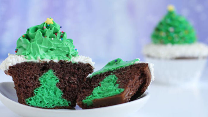 chocolate cupcake with white and green icing shaped like x-mas tree, cut in half to show green x-mas shape inside, on white plate with another cupcake in background