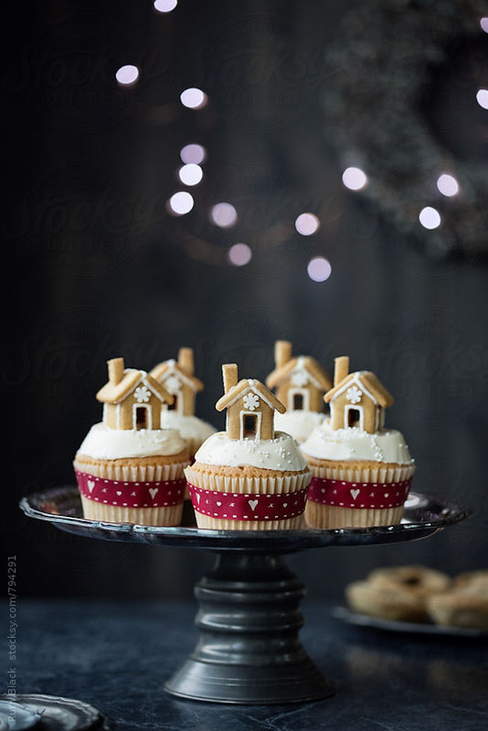 batch of cupcakes with white frosting, decorated with small gingerbread houses, tied with red festive ribbons, on black dish placed on table