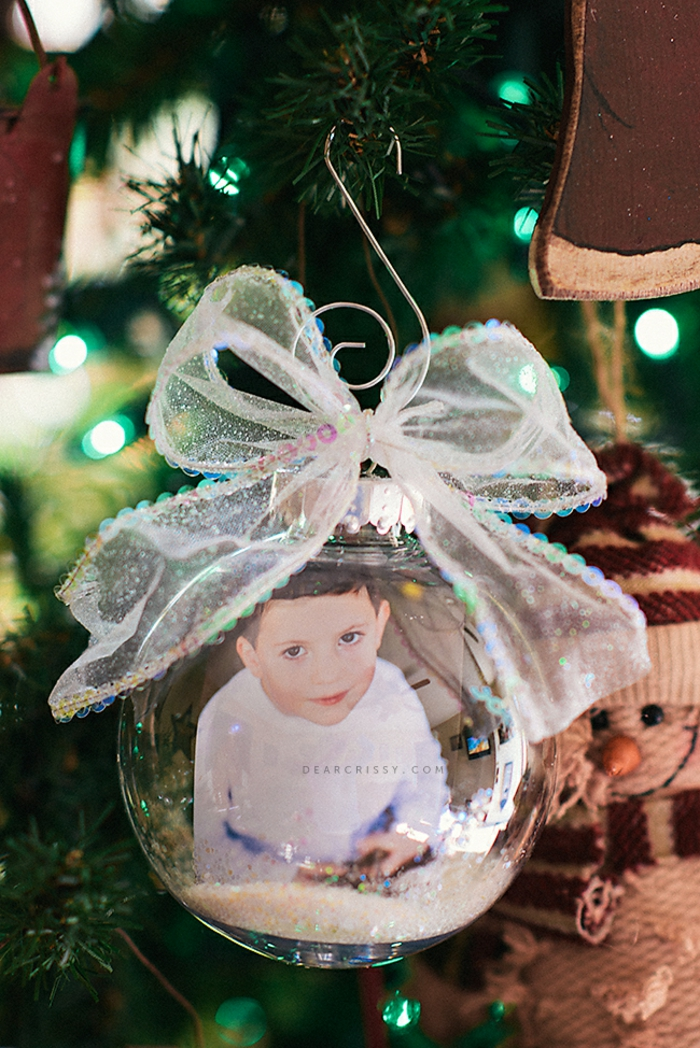 cheap christmas gift ideas, a photo of a small boy inside a clear glass christmas bauble with some glitter, tied with a sheer sparkling ribbon, attached to a tree with a metal hook