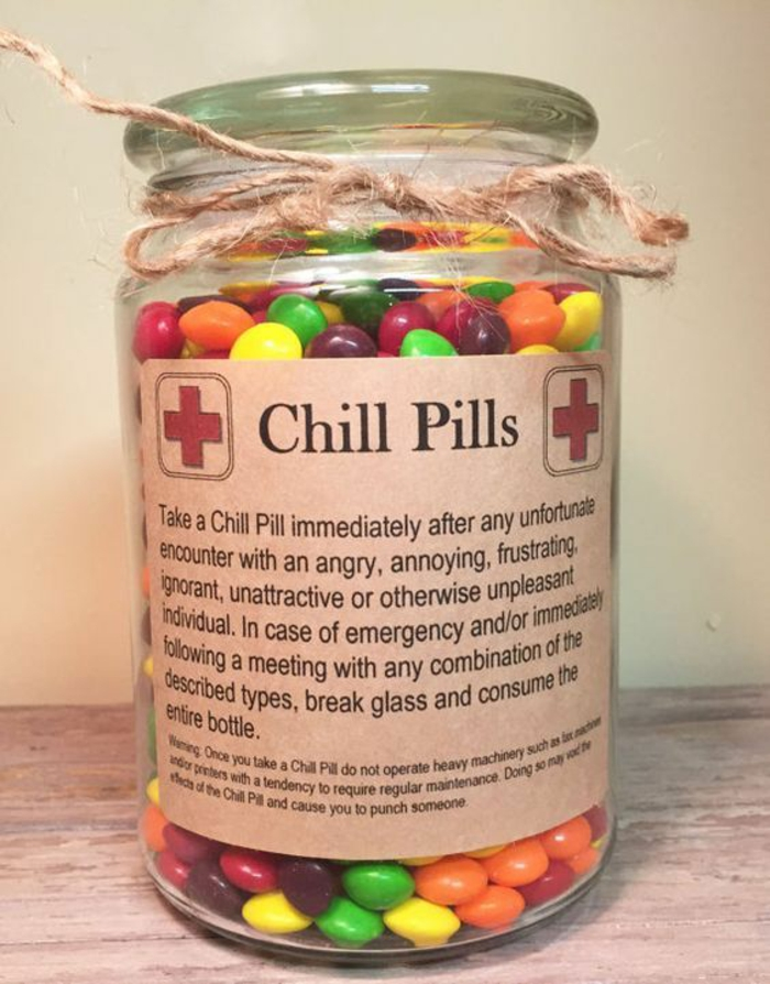 xmas gifts, a clear jar containing many colorful candies, tied with simple string, with a sticker featuring medical crosses and saying chill pills