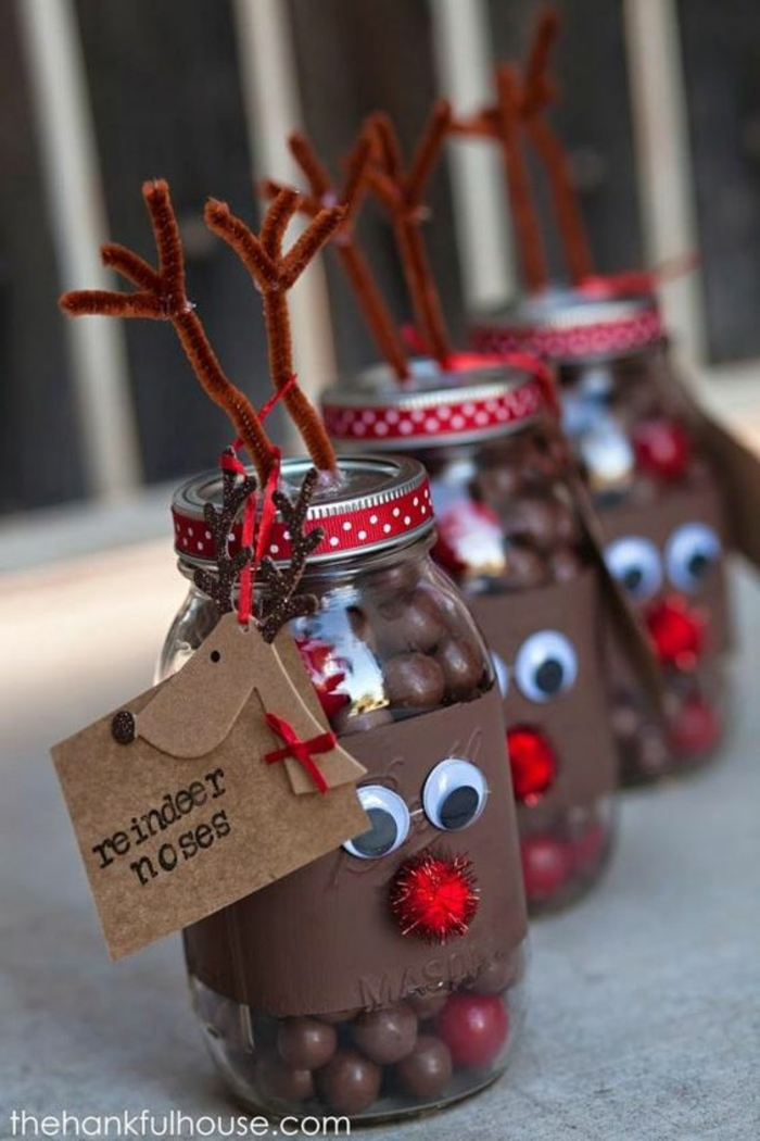family christmas gifts, three mason jars decorated with a brown paper strip, with googly eyes and red a pom-pom nose, with wire antlers stuck on lids, red dotted ribbon and carboard label