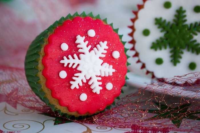mini cupcake recipes, close up of cupcake in green wrapper, with red fondant icing and white snowflake, near cupcake with red wrapper and white icing with green snowflake