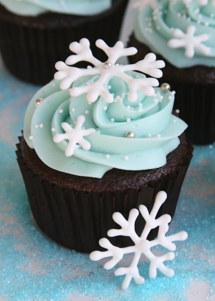 christmas flavors, chocolate cupcake with black wrapper, light blue frosting, decorated with snowflake shapes, white sprinkles and silver pearls