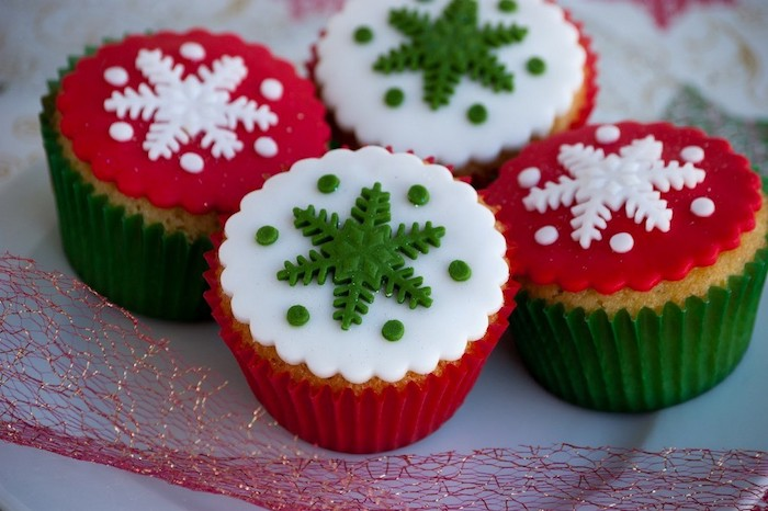 mini cupcake recipes, four cupcakes with white red and green fondant icing, in red or green wrappers, decorated with green or white fondant snowflakes