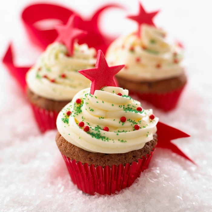 christmas baking ideas, three light brown cupcakes, pale yellow creamy frosting and red wrappers, decorated with red pearls and stars and green sprinkles