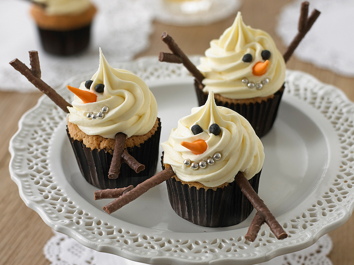 christmas flavors, three cupcakes with dark wrappers, decorated with white frosting, with silver pearls, small fondant shapes and chocolate details, made to look like snowmen, on white plate