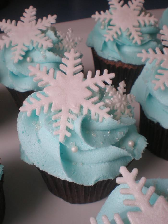 holiday cupcakes, several cupcakes with dark wrappers, light blue frosting, decorated with white snowflakes sprinkles and pearls