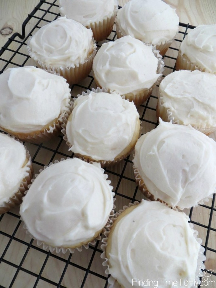 cupcake ideas, twelve light-colored cupcakes, with white creamy frosting, on black metal oven grate
