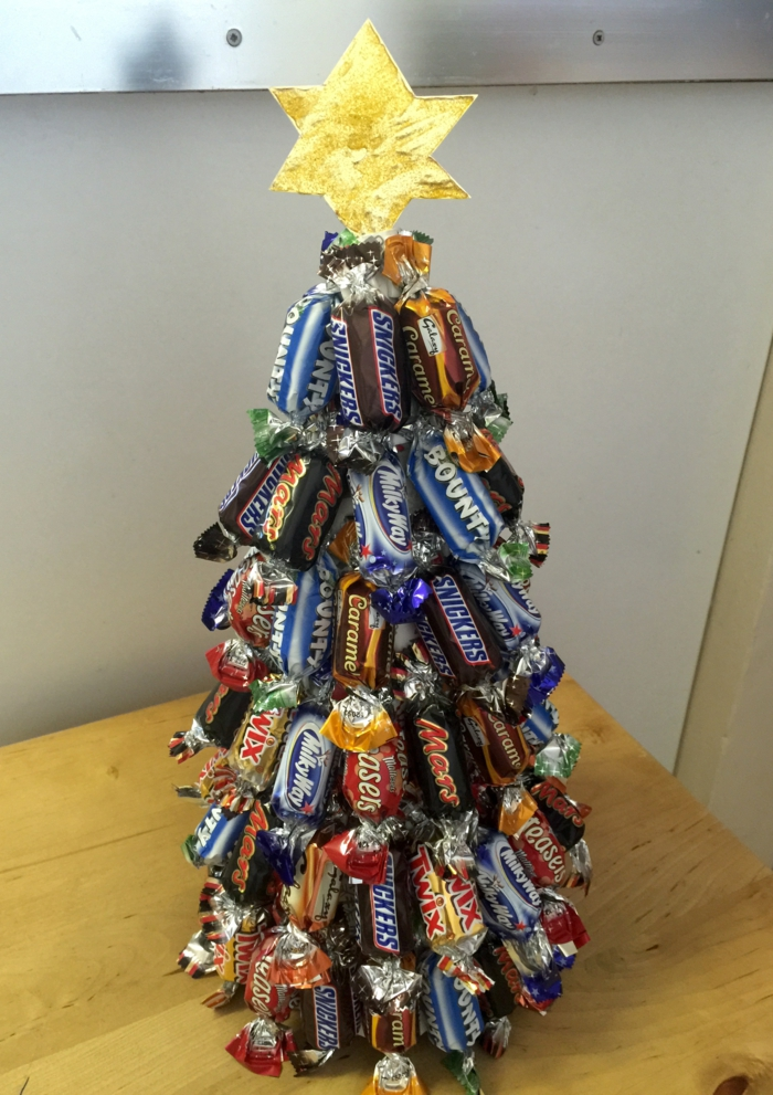 christmas tree made of miniature candy bars, with a six pointed paper star in gold, placed on wooden desk with light background