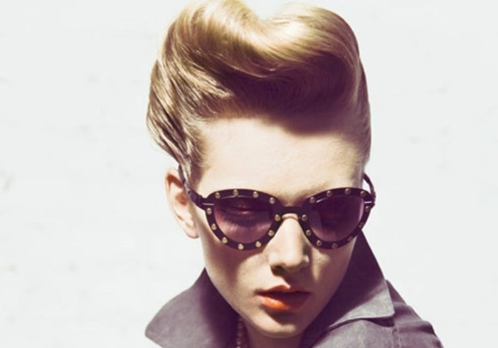 blonde woman with gelled up retro hair, dark sunglasses with metal studs, orange lipstick and a grey top, white background